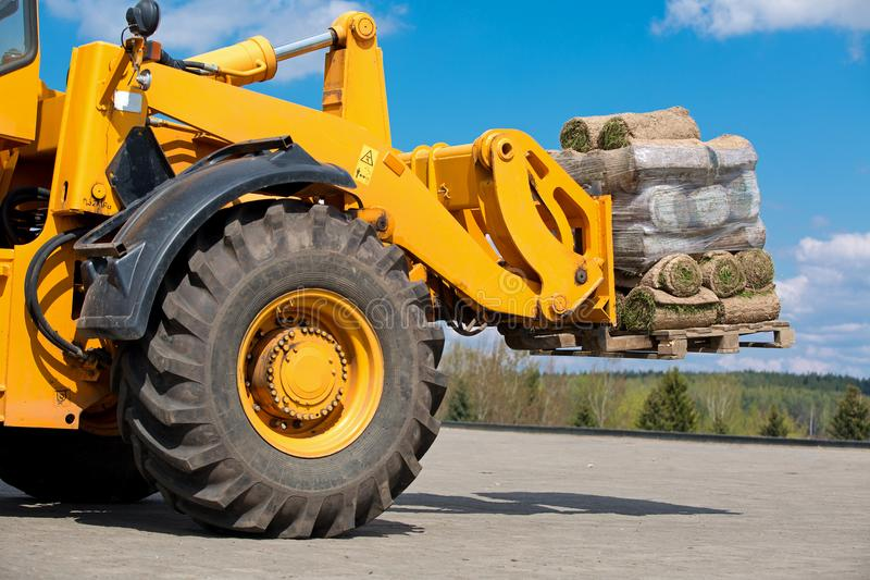 Wheel loader moving cargo green grass lawn rolls royalty free stock photo