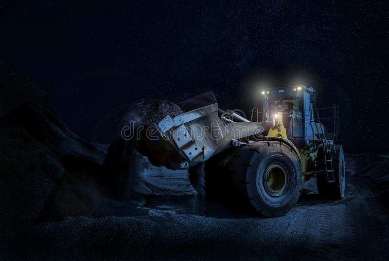 Wheel loader Scooping Gravel on a night time construction project stock images