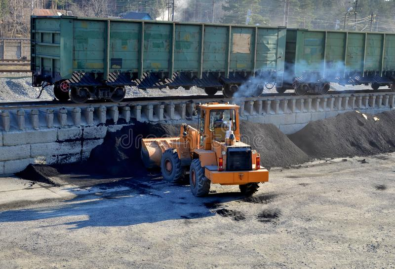 Loader unload coal at a cargo railway station in a mining quarry royalty free stock photos