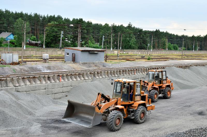 The wheel loader unloads crushed stone in a gravel pit. Unload bulk cargo with of the cargo railway platform in the mining quarry - Image stock image
