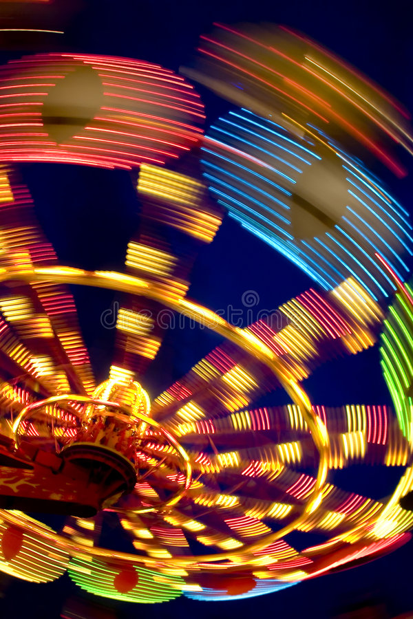 Wheel in motion. Ferris wheel illuminated at night in amusement park