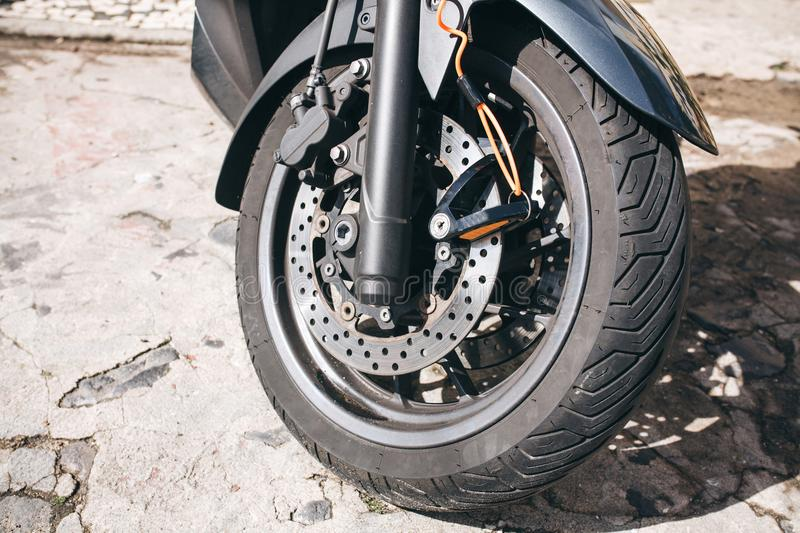 Wheel of motorcycle or scooter or moped. Brake system and spare parts for bike. Wheel of motorcycle or scooter or moped. Autotire or tire and design of wheel of stock photography