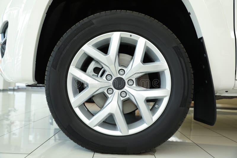 Wheel of new luxury white car in  auto dealership, closeup. Wheel of new luxury white car in modern auto dealership, closeup stock photography
