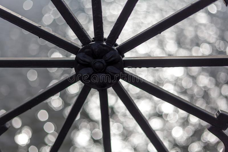 Wheel with radial elements. Round design with radial rays on a blurry shiny background stock image