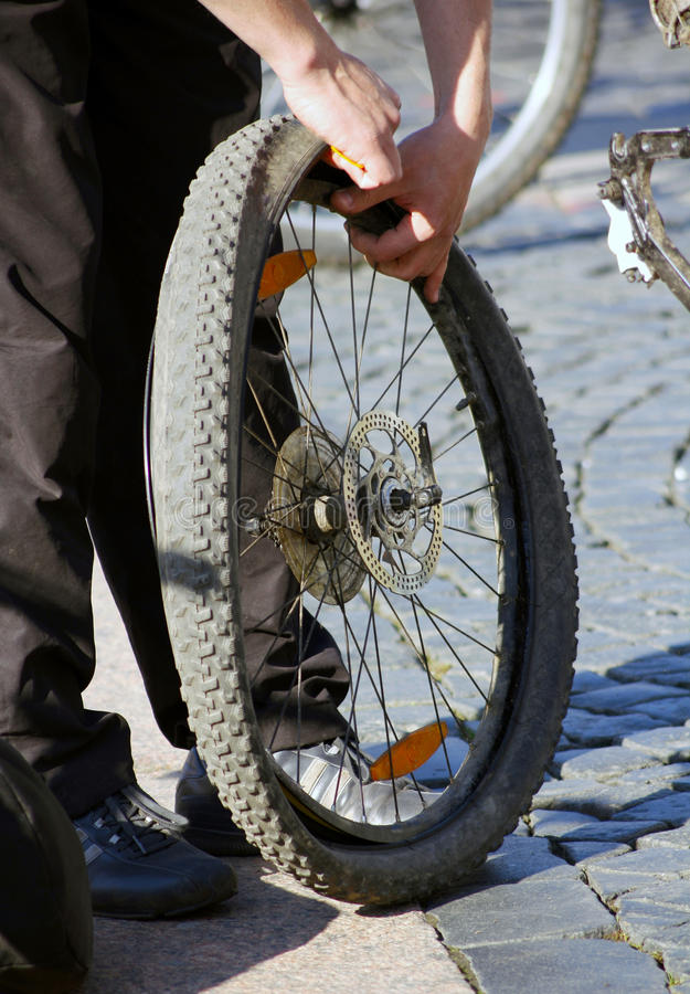 Wheel repair. Man changes punctured inner tube of bicycle stock photography
