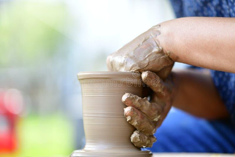 Wheel-throwing. Ceramic artist is wheel-throwing to make greenware