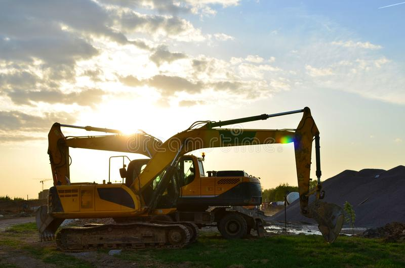 Wheel and tracked heavy excavators working at construction site. hydraulic excavator crane at building site on sunny day stock photo