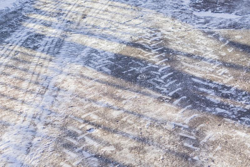 Wheel tracks on the winter road covered with snow in a sunny day royalty free stock photography