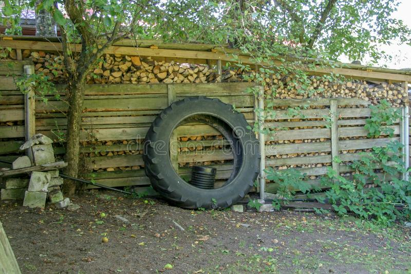 The wheel from the tractor is leaning against the woodpile. stock photo