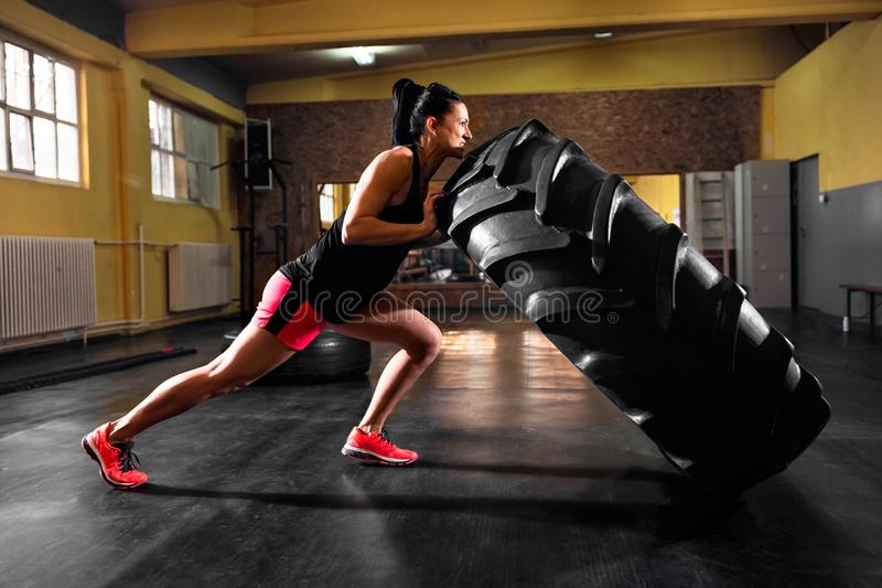 Wheel truck exercises at gym by young muscular woman. Wheel truck exercises at gym by young strong muscular woman royalty free stock photo