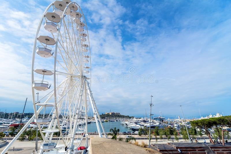 Wheel and Vauban port in Antibes. Antibes, France - July 01, 2016: day view of port Vauban and grande roue in Antibes, France. Port Vauban is the largest marina stock photo
