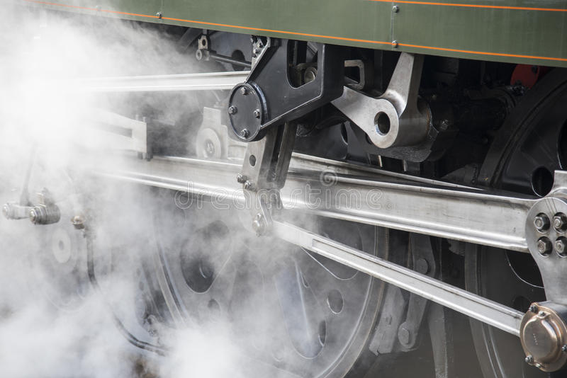 Wheel of vintage rail locomotive with steam. Wheel with rods and pistons on green steam rail locomotive in close-up with steam coming to the left royalty free stock photo