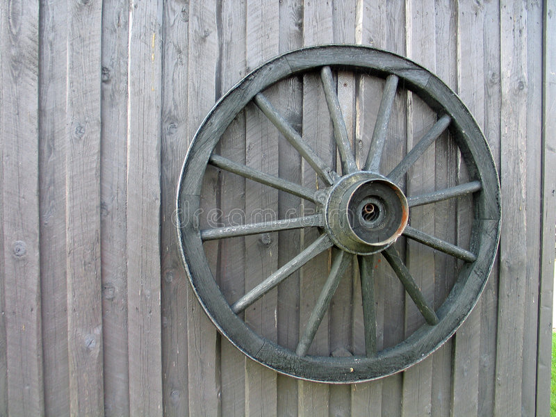 Wheel of a wagon. Wooden wagon wheel on an old barn door royalty free stock images