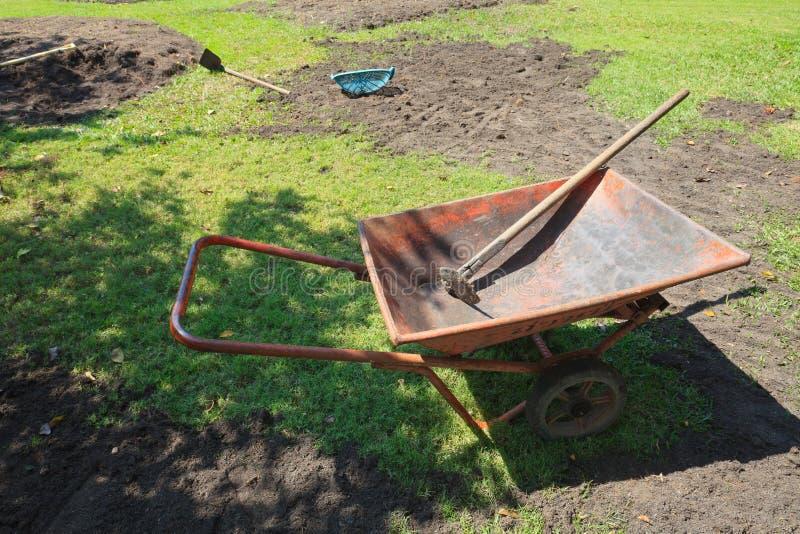 Wheelbarrow και δίσκοι με νέο να προετοιμαστεί κήπων στοκ εικόνα με δικαίωμα ελεύθερης χρήσης