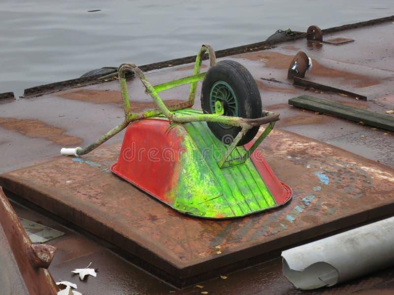 Wheelbarrow malował zieleni i czerwieni kłaść do góry nogami na ośniedziałej łodzi obrazy stock