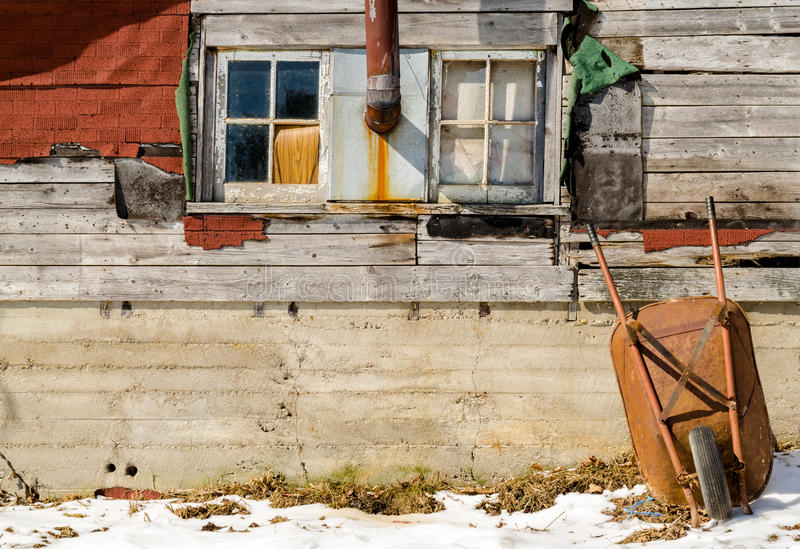 Wheelbarrow resting on a colorful old house wooden wall in winter time stock photos
