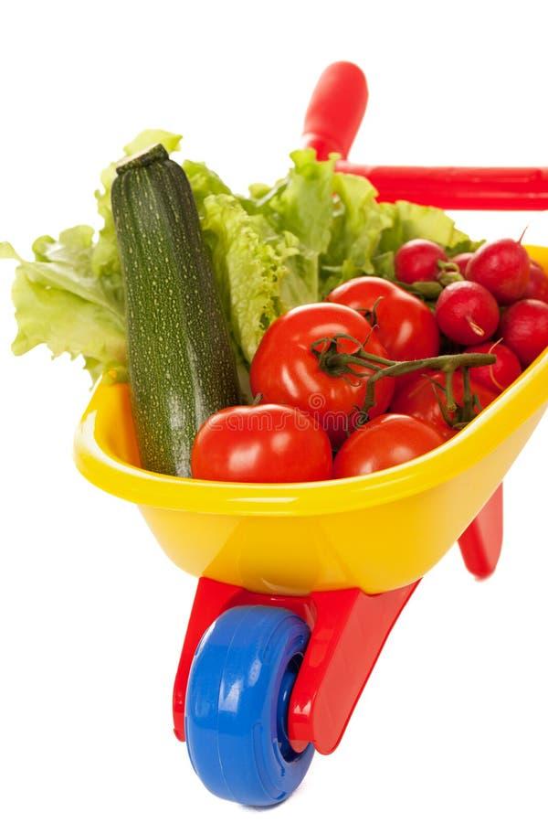 Wheelbarrow with vegetables. Isolaed on white stock photos