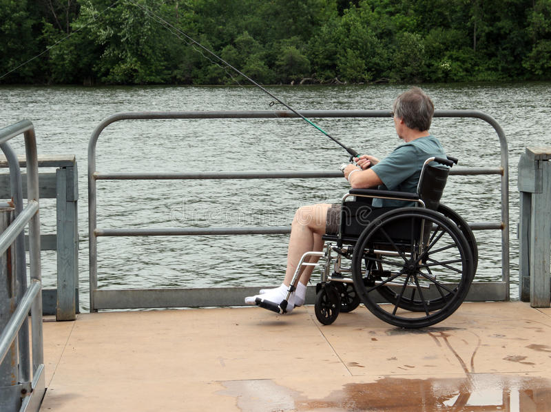 Wheelchair accessible fishing dock. Man in a wheelchair fishing from a handicapped accessible fishing pier royalty free stock photo
