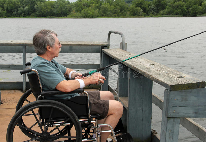 Wheelchair accessible fishing pier. Man in a wheelchair fishing from a handicapped accessible fishing pier stock photo