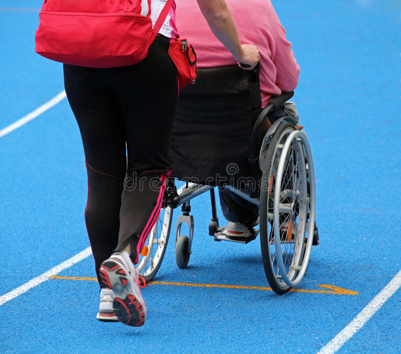 Wheelchair with an attendant on the athletic track during the sp. Mobility wheelchair with an attendant on the athletic track during the sporting event royalty free stock photography