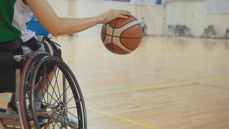 Wheelchair basketball player dribbling the ball quickly during training of disabled sportsmen. Close up stock photos