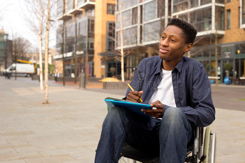 Young Male Disabled Student In A Wheelchair Thinking Stock Photo