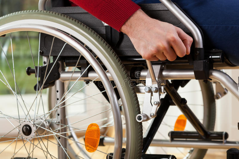 Wheelchair breaks. Close-up of disabled man using wheelchair breaks stock image
