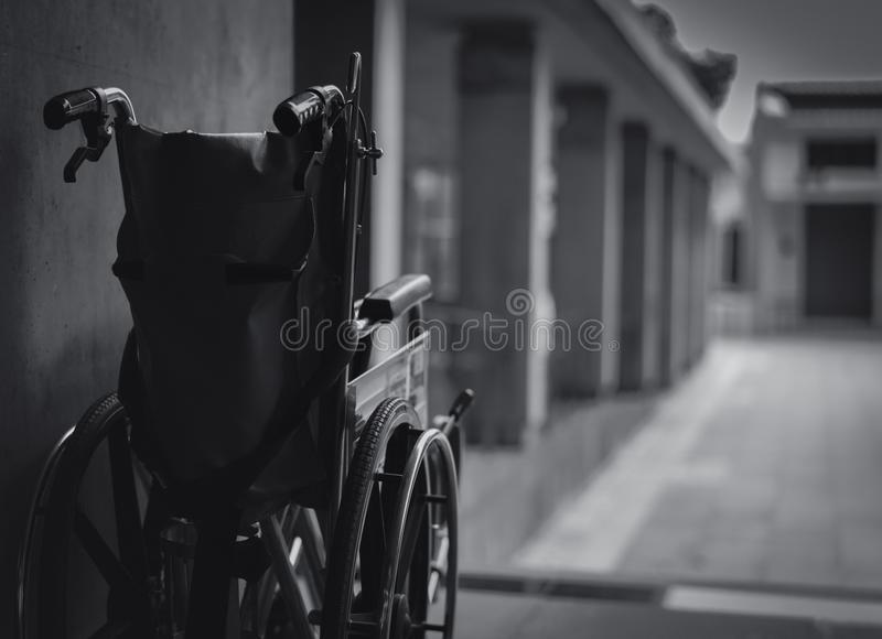 Wheelchair folded beside the wall. Sad news at the hospital concept. Depression with aging society. Lonely empty wheelchair. stock photography
