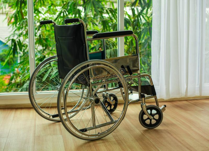 Wheelchair hospital window. Wheelchair seat of the hand wheel. To propel itself the main component is seated at the foot wheel, two small front wheels. big wheel royalty free stock photo