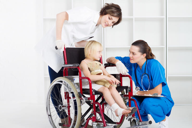 Wheelchair patient. A female doctor and nurse chatting to a little wheelchair patient with a bandaged foot royalty free stock images