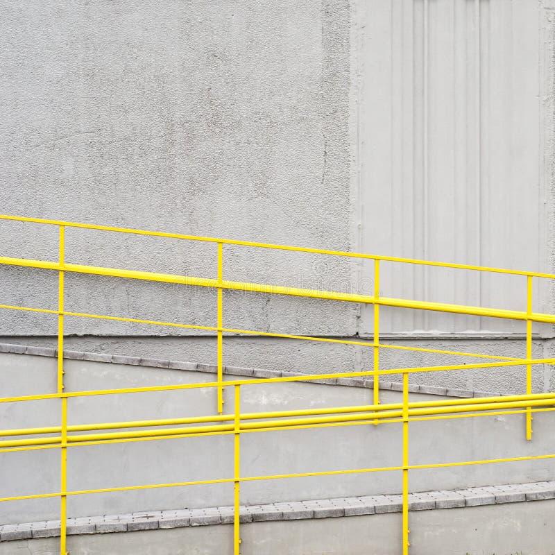 Wheelchair ramp. Yellow wheelchair ramp near the grey wall stock photos