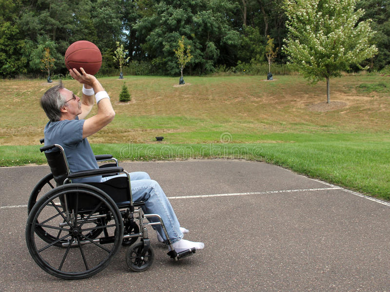 Wheelchair Sports. Disabled man in a wheelchair playing basketball royalty free stock image
