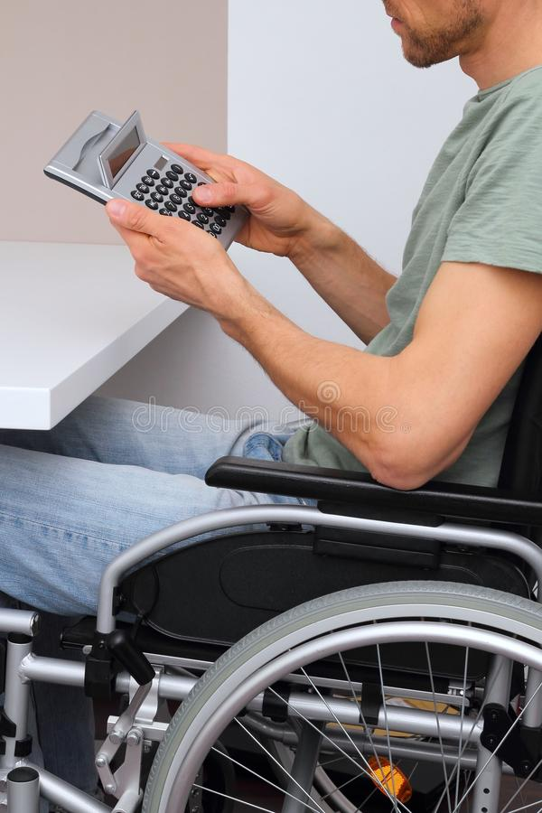 Wheelchair user with calculator. A Wheelchair user with calculator stock photo