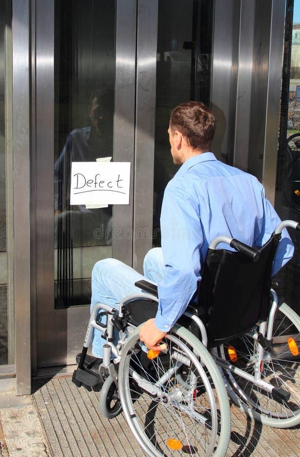 Wheelchair user on defect elevator door. A Wheelchair user on defect elevator door royalty free stock photos