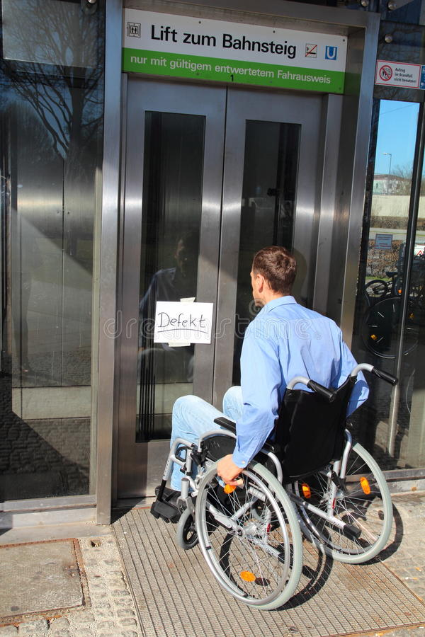 Wheelchair user on a defect lift. A Wheelchair user on a defect lift royalty free stock images