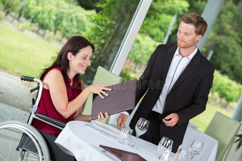 Wheelchair user dinning at restaurant. Wheelchair user dinning at a restaurant stock photos