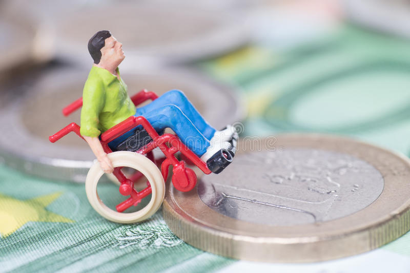 Wheelchair user. With euro coins and euro banknote stock photography