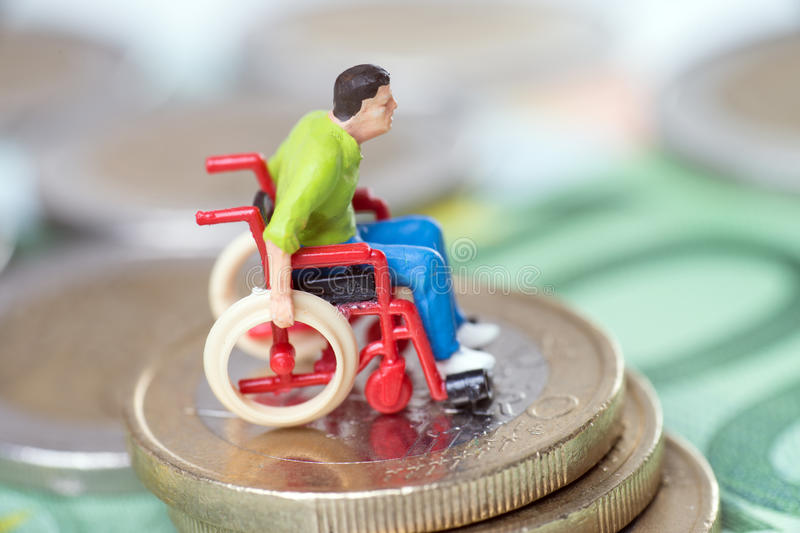 Wheelchair user. With euro coins and euro banknote royalty free stock photos