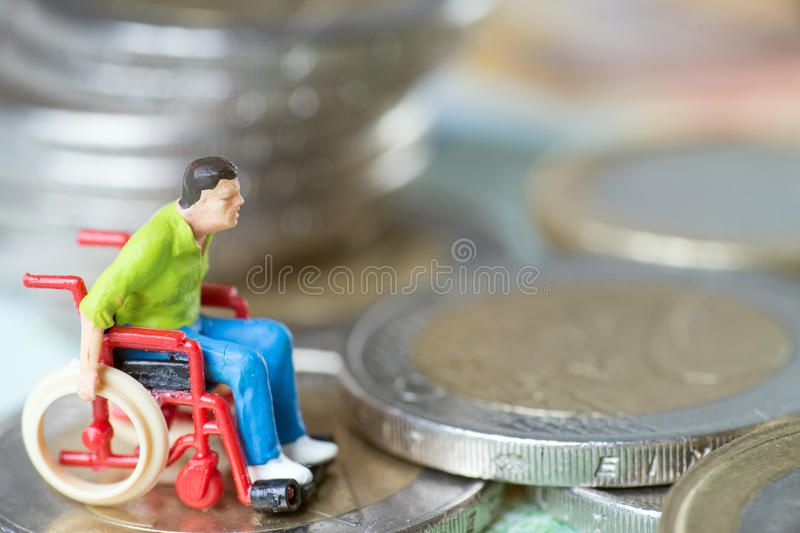 Wheelchair user. With euro coins and euro banknote stock photo