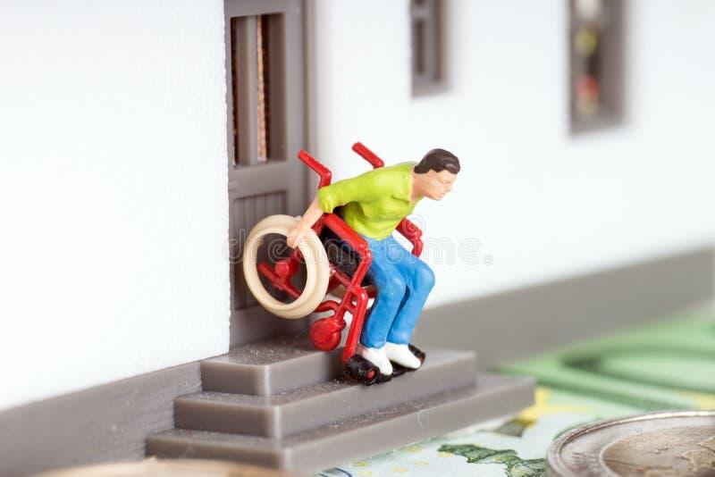 Wheelchair user. On an exterior staircase and euro money royalty free stock photos