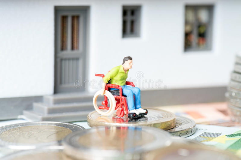 Wheelchair user. In front of a house stock photography