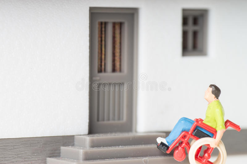 Wheelchair user. In front of a house stock images