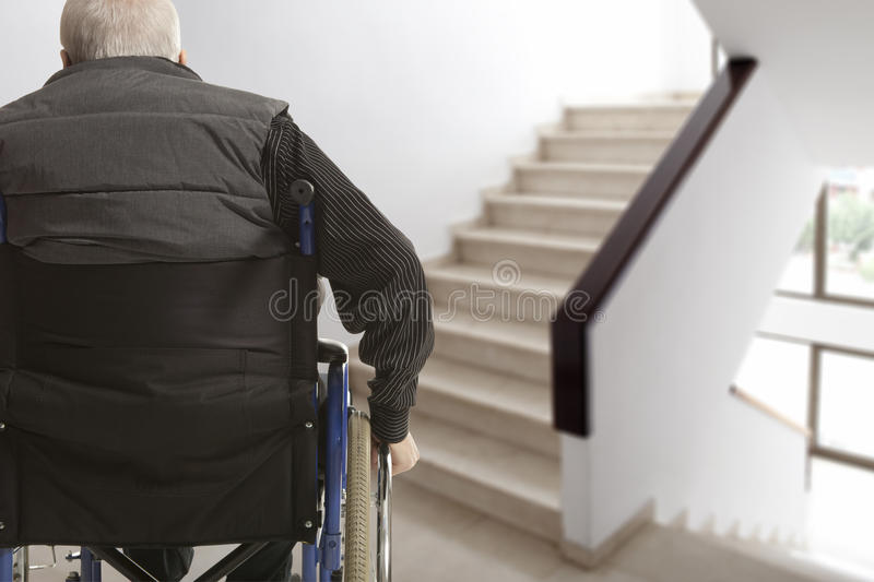Wheelchair user. In front of staircase barrier royalty free stock photos