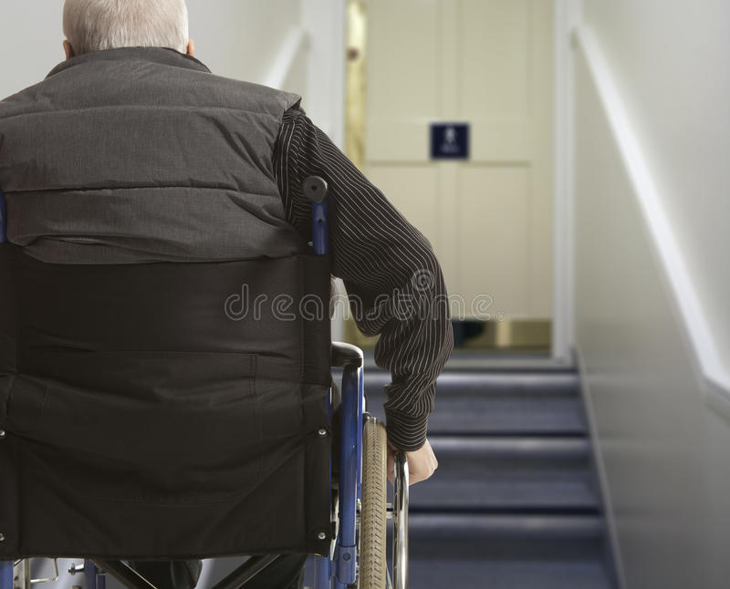 Wheelchair user. In front of staircase barrier royalty free stock photography