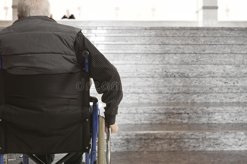 Wheelchair user. In front of staircase barrier stock photo