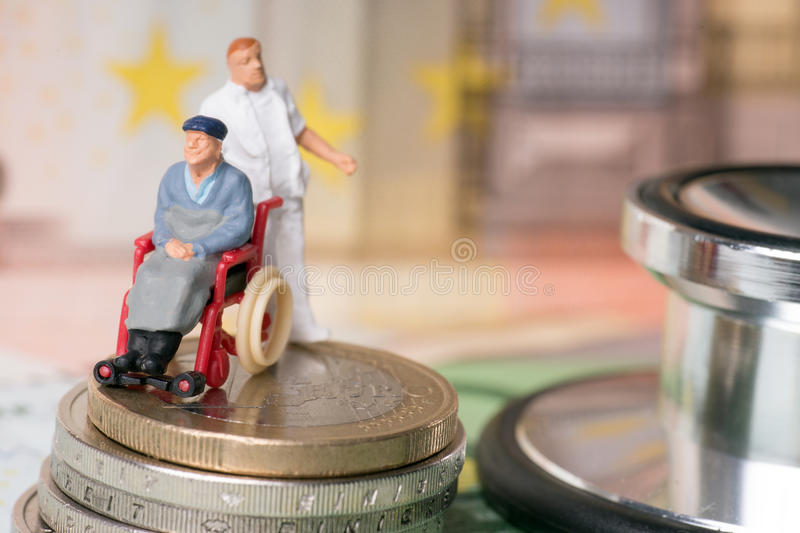 Wheelchair user. With nursing staff and euro money with stethoscope stock photos