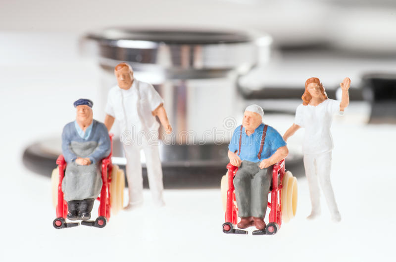 Wheelchair user. With nursing staff and stethoscope over a white background royalty free stock image