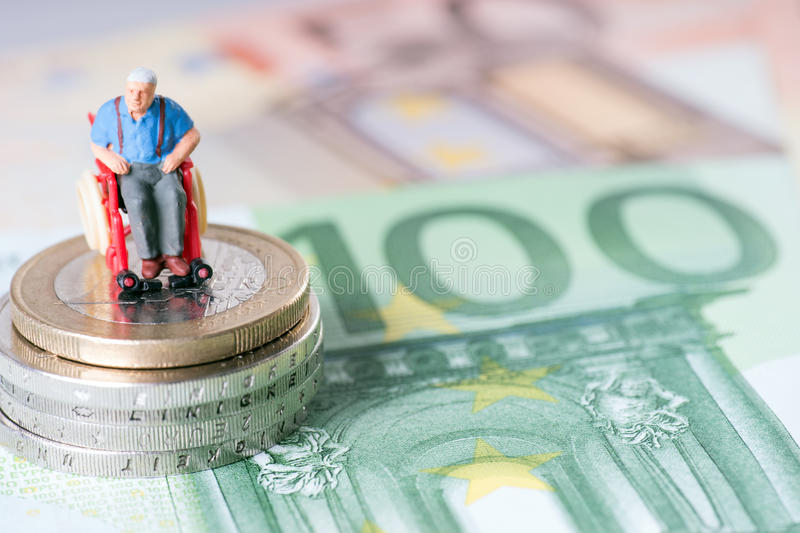 Wheelchair user. Old man in a wheelchair with money royalty free stock image