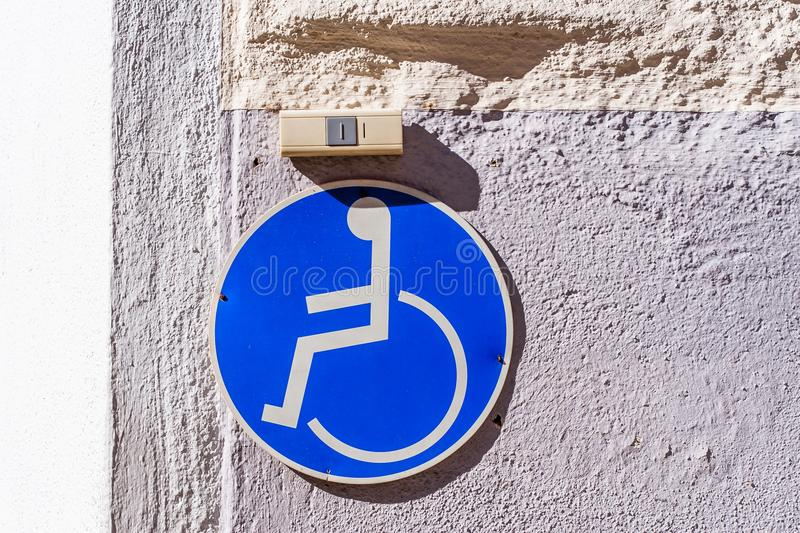 Wheelchair user sign and ring above it. Wheelchair user sign and ring above it on an facade in front of an entrance stock photography