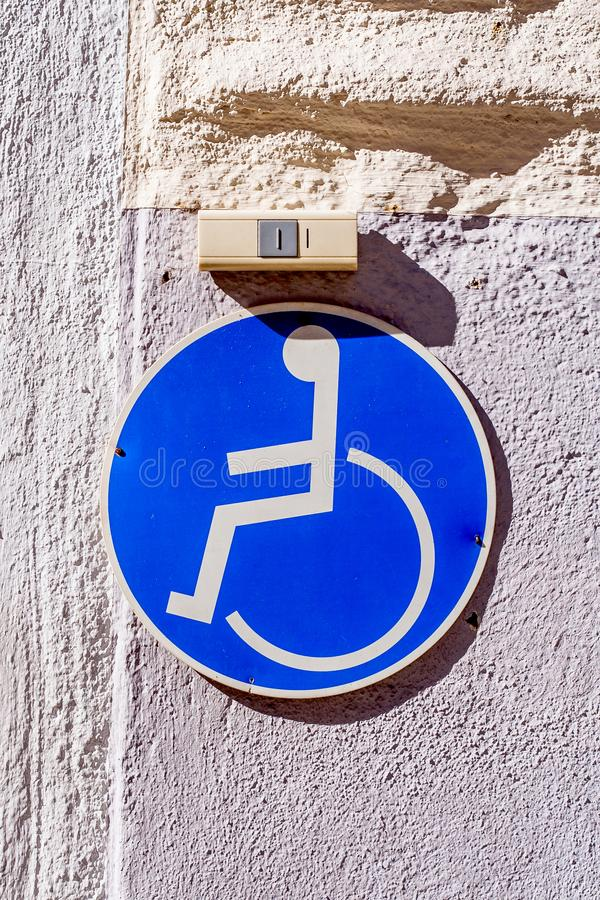 Wheelchair user sign and ring above it. Wheelchair user sign and ring above it on an facade in front of an entrance royalty free stock image